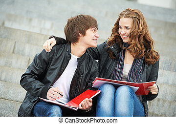 Two smiling young students studying outdoors