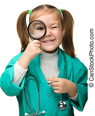 Cute little girl is playing doctor looking through...