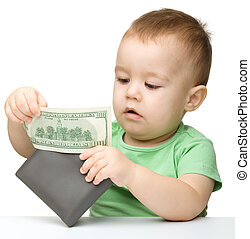 Little boy is playing with dollars