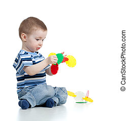 child boy playing with color toy over white background