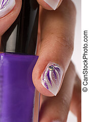 Nail lacquer - Beautifully decorated hand holding a bottle...