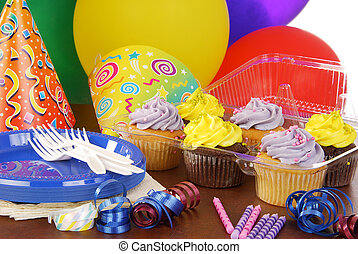 Birthday party cupcakes - A table set with party favors and...