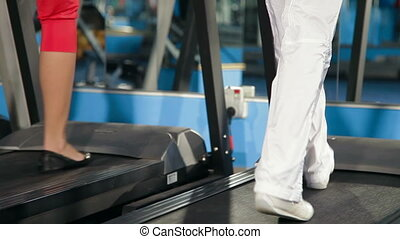 Exercising In The Gym On Treadmill - Young Women Practicing...