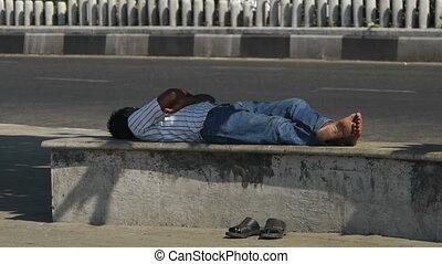 Man sleeping on a street bench