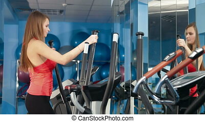 Young Girl On Cross Trainer At The Gym Exercising