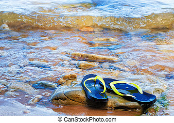 Rubber slippers on the pebble sea coast