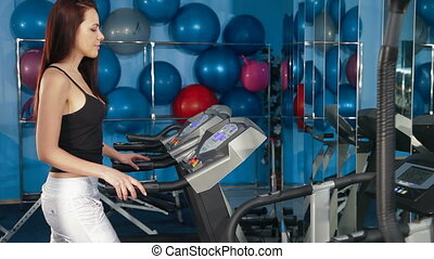 Young Woman Training On Treadmill In The Gym Looking At...
