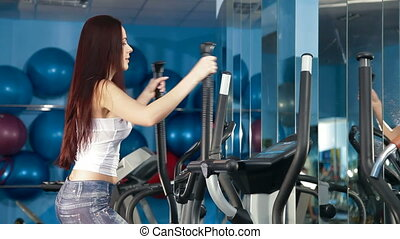 Exercise In The Gym - Young Woman Training On Cross Trainer...