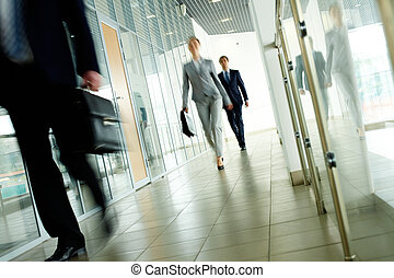 Walking people - Businesspeople going along corridor inside...