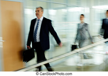 Office life - Businessman going along corridor with walking...