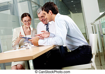 Sharing ideas - Three business partners sitting in office...