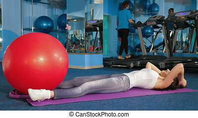 Fitness Club - Young Women Exercising At The Gym Looking At...
