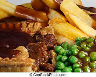 Close up of Steak Pie and chips with peas and gravy.