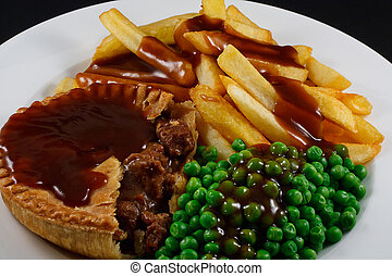 Close up of Steak Pie and chips with peas and gravy. A...