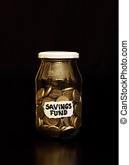 British Pound Coins in Jar - Labelled savings jar containing...