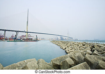 Bridge with cargo ships in Hong Kong at day