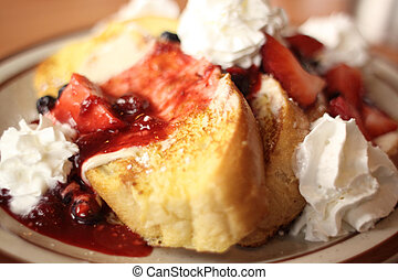 French toast with strawberries and blueberries and whip...