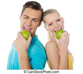 Couple eating apple back to back - Couple posing back to...