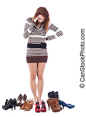 Puzzled woman - Woman is trying to decide which shoes to...
