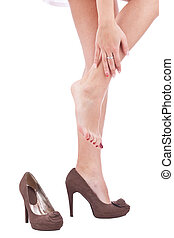 Women wearing high heels brown shoes, massaging tired legs