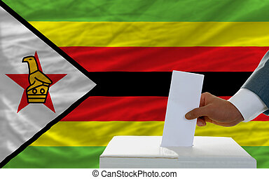 man voting on elections in zimbabwe in front of flag - man...