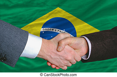 businessmen handshake after good deal in front of brazil...