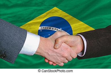 businessmen handshake after good deal in front of brazil...