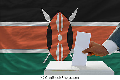 man voting on elections in kenya in front of flag - man...