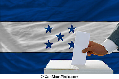 man voting on elections in honduras in front of flag - man...