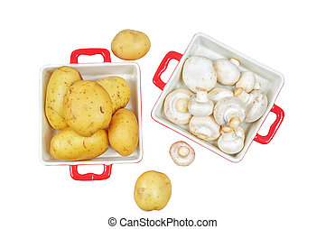 Raw mushrooms and potatoes in red trays, isolated