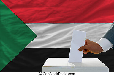 man voting on elections in sudan in front of flag