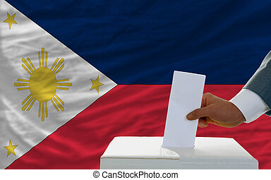 man voting on elections in phillipines in front of flag