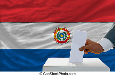 man voting on elections in paraguay in front of flag