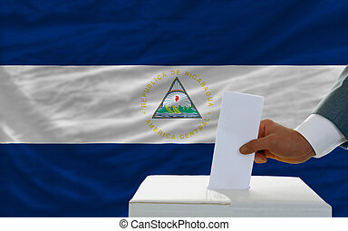 man voting on elections in nicaragua in front of flag