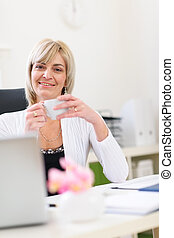 Smiling senior business woman having coffee break