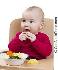young child eating in high chair - young child in red shirt...