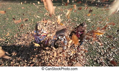 Windy autumn - Children playfully throwing autumn leaves at...