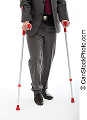 Businessman Walking On Crutches - Lower body of a disabled...