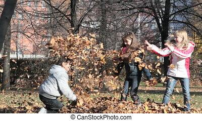 Autumn park fight - Playful children making a mess in an...