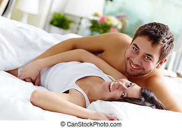 Joyful couple - Happy young couple lying in bed and looking...