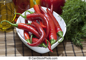 chilis - chili peppers on plate next to fresh dill