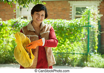 Female gardener fertilizes the soil