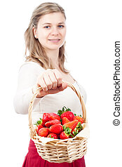 Happy woman holding basket with strawberries