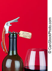 A corkscrew with cork on the top of bottleneck beside of a glass of red wine