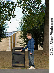 Teenager putting rubbish in a bin