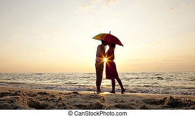 Couple kissing under umbrella at the beach in sunset.