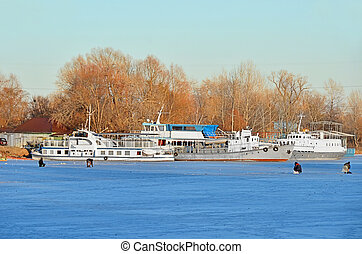 Ship at small river harbor at winter