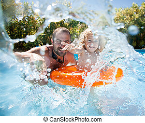 Child with father in swimming pool - Happy family playing in...