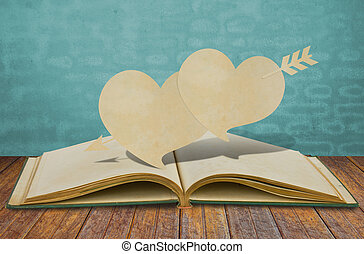 Paper cut of two heart and arrow on old book