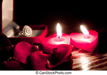 Valentines candles on rose petals background